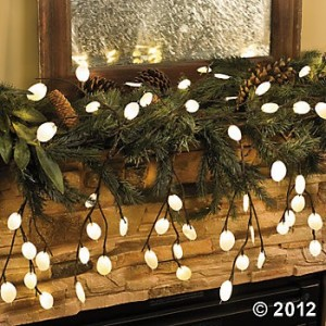 Lighted branches with evergreen boughs on mantle