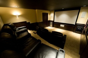 Home theater with rows of seating and a wall sconce